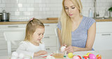 Cheerful girl painting eggs with mother