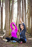 two women doing yoga in the middle of the woods