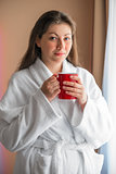 portrait girl in bathrobe with a cup near the window