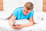happy man with an alarm clock in hands in bed