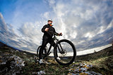 Photo below of the mountain cyclist in the black sportwear on the rocks against dramatic sky with clouds.