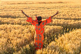 African woman in traditional clothes arms raised in field of cro