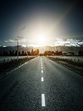 road to the alps with dramatic sun light