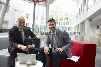 Portrait Of Businessmen Meeting In Lobby Of Modern Office