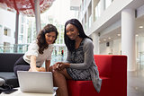 Two Businesswomen Meeting In Lobby Area Of Modern Office