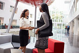 Two Businesswomen Shaking Hands In Lobby Of Modern Office