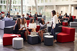 Businesswomen Meeting In Busy Lobby Of Modern Office