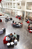 Students sitting in university atrium, vertical