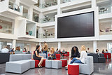 Students sit talking under AV screen in atrium at university