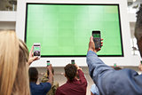 Students photograph screen with phones, back view, close up