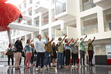 Students in a university atrium taking photos with phones
