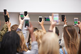 Young adults with arms raised take pictures with smartphones