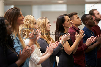 Adult students applauding at an event in their university
