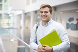 Smiling Caucasian male student in modern university building