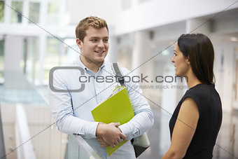 Adult student and teacher talking in university foyer