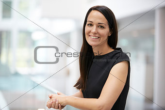 Portrait of young woman in modern university interior