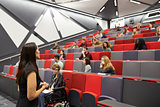 Woman lecturing students in a university lecture theatre