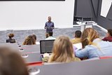 Man lectures students in lecture theatre, back row seat POV