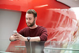 Bearded male student using smartphone in university building