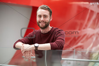 Bearded male student in modern university building, portrait