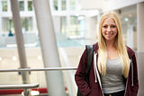 Smiling blonde haired female student in university building