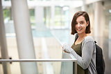Smiling dark haired female student in university building