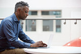 Middle aged black man using laptop, close up side view