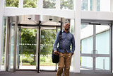 Middle aged black man in the foyer of a large modern building