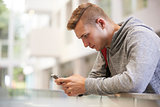 Young adult male student uses smartphone in university lobby