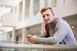 Young adult male student looks to camera in university lobby