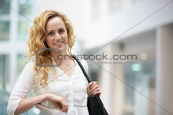 Blonde haired young woman leaning in modern interior
