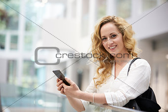 Blonde haired young woman uses smartphone in modern interior