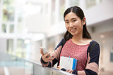 Asian female adult student using phone looks to camera