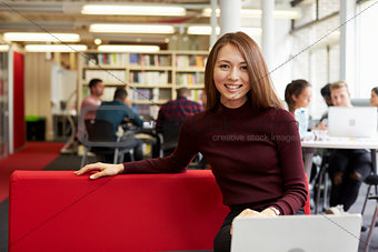 Portrait Of Female University Student Working In Library