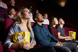 Young Couple In Cinema Watching Film And Eating Popcorn