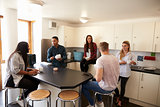 Students Relaxing In Kitchen Of Shared Accommodation