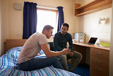 Male Students Working In Bedroom Of Campus Accommodation
