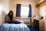 Student Uses Mobile Phone In Bedroom Of Campus Accommodation
