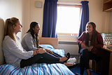 Female Students Relaxing In Bedroom Of Campus Accommodation