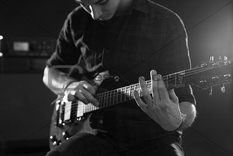 Close Up Of Man Using Tapping Technique On Electric Guitar