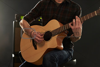 Close Up Of Man Playing Amplified Acoustic Guitar