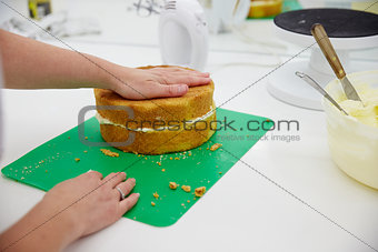 Close Up Of Woman In Bakery Preparing Cake For Decoration