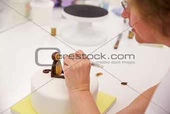 Close Up Of Woman In Bakery Making Monkey Cake Decoration