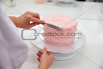 Close Up Of Woman In Bakery Decorating Cake With Icing