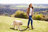 Mature Woman Taking Golden Retriever For Walk In Countryside