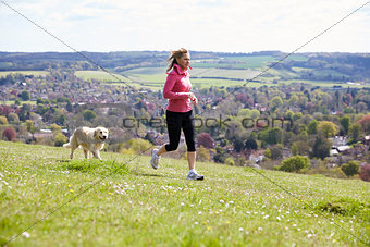 Mature Woman With Golden Retriever Jogging In Countryside