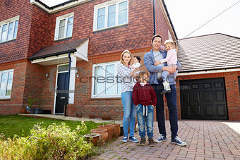Portrait Of Young Family Standing Outside New Home