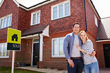 Portrait Of Young Couple Standing Outside New Home