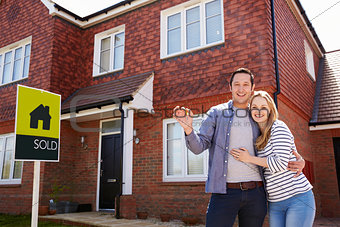 Portrait Of Young Couple With Keys To New Home
