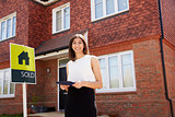 Female Realtor Standing Outside Residential Property